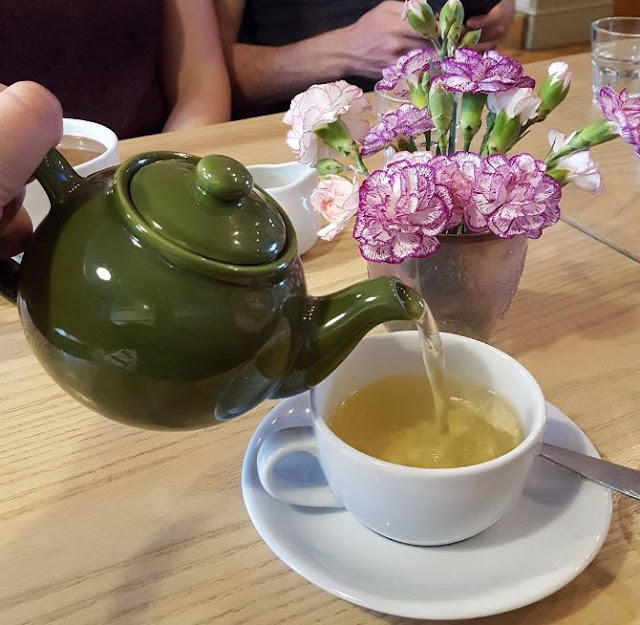 green teapot pouring loose leaf tea