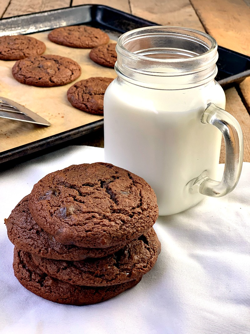 Photo of Keto Double Chocolate Chip Cookies on a white plate with a mason jar of milk next to the plate and cookies on a cookie sheet in the background.