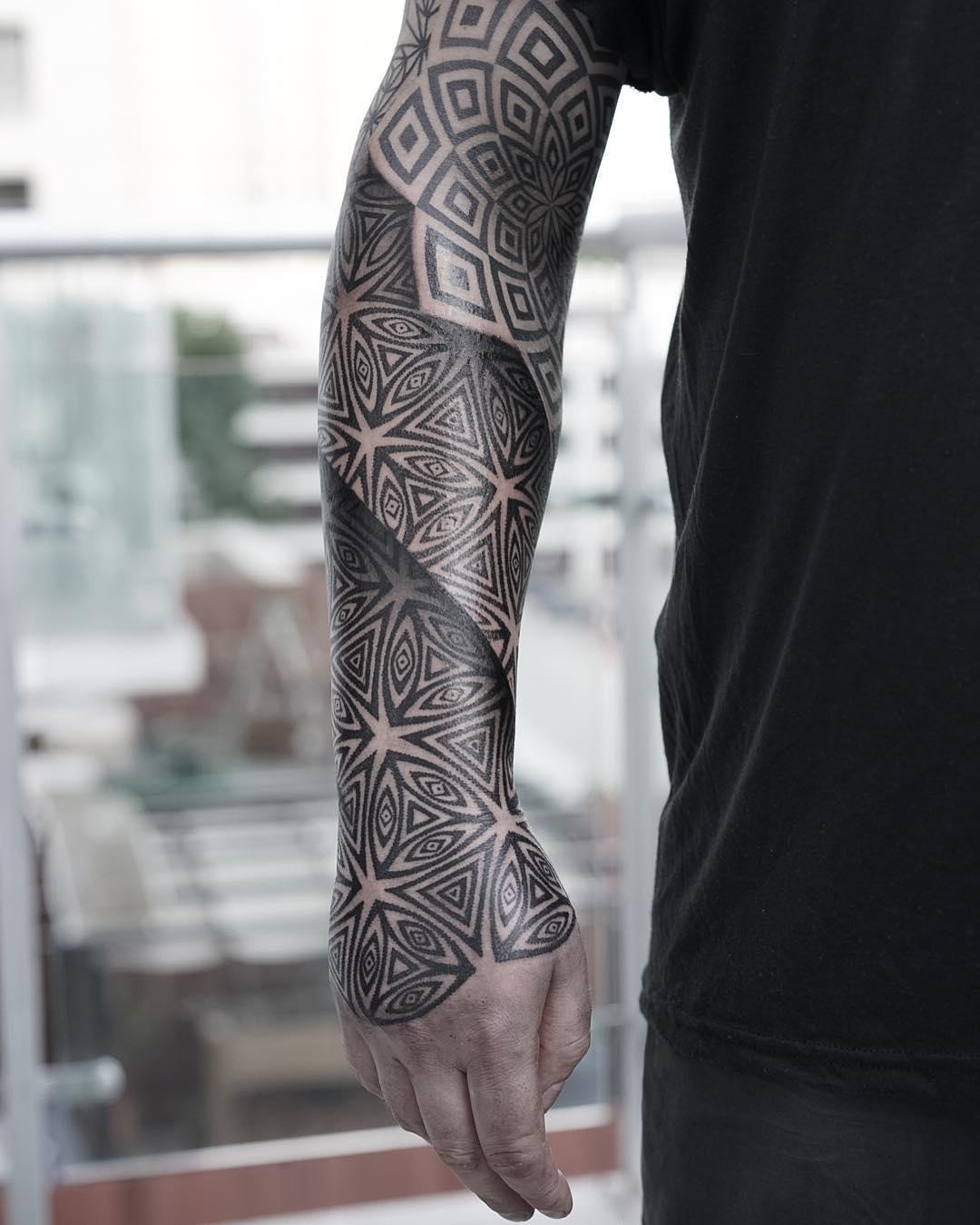 Un tatuaje geometrico en blanco y negro en el brazo de un hombre