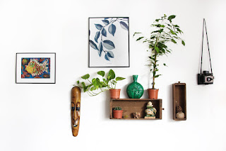 Pictures, knickknacks and plants on little shelves.