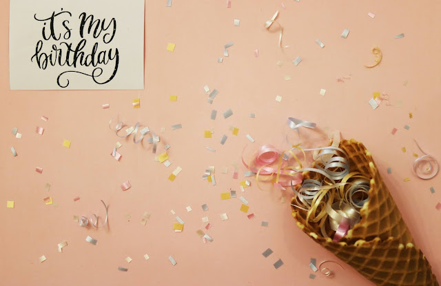 "The image shows a pink background covered in confetti. There is an ice cream cone in the right corner with streamers spilling out from it. In the top left corner, there is a white card saying ""it's my birthday!"""