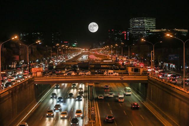 Mặt Trăng mọc trên một con đường tấp nập ở thành phố Bắc Kinh, Trung Quốc. Hình ảnh: Rex Images.