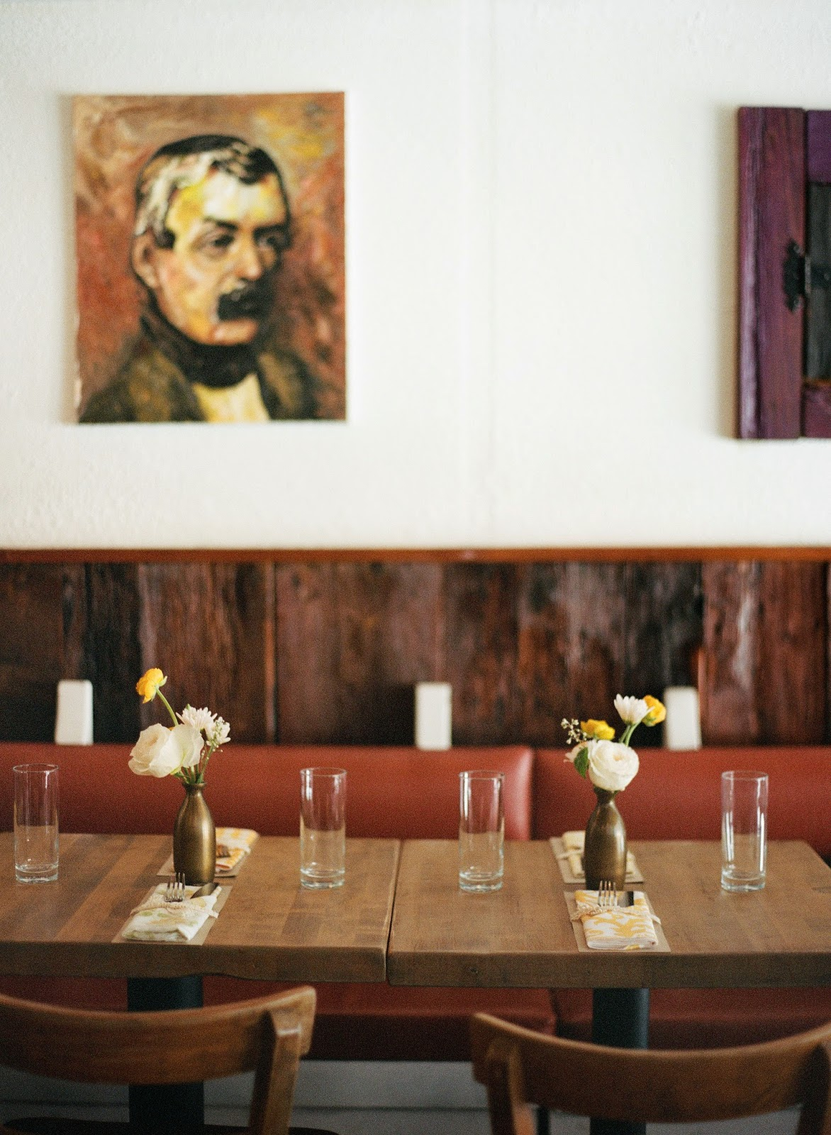yellow and white spring wedding flowers in antique brass vases with vintage portraits at an intimate brooklyn, new york restaurant wedding dinner