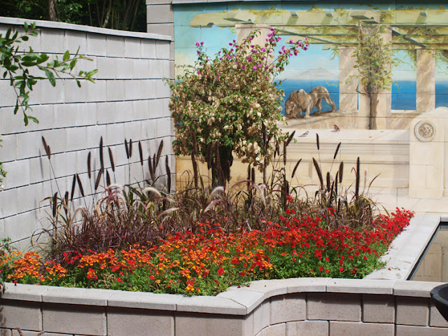 Showhave med vægmalerier og høje bede i brændte farver