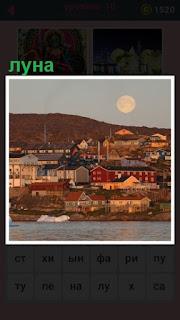 над небольшим городком висит в небе луна