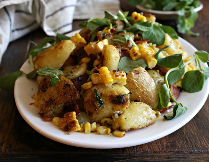 Recipe for a roasted potato salad with corn, bacon and an olive oil dressing.