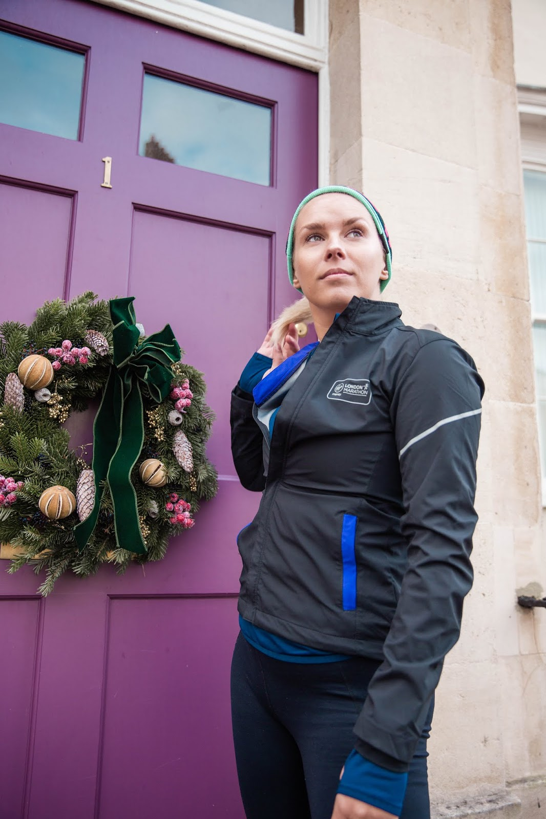 Rachel Emily in running gear stood near a festive door wreath looking away from the camera - Rachel Emily Blog