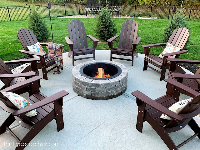 round fire pit with Adirondack chairs