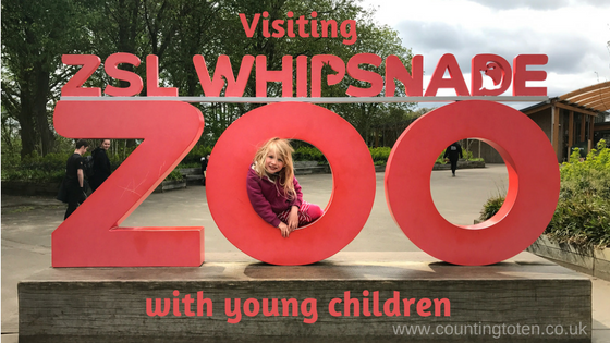 "The red entry sign to the Zoo which says ""ZSL Whipsnade Zoo"" with text before it saying ""visiting"" and afterwards ""with young children"""