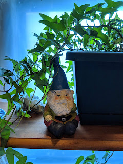 Shelf sitting gnome figurine gesturing a finger towards his nose.