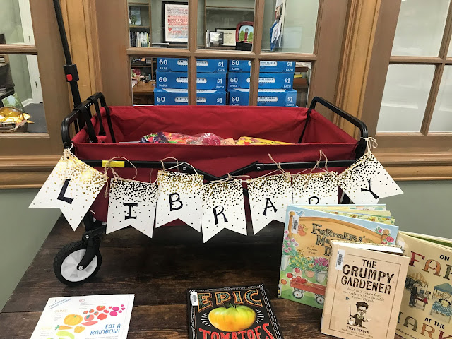 A red wagon sits in the middle of a library. A sign on the wagon says library and colorful books are in the wagon. Books about gardening are displayed in front of the wagon.