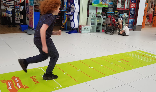 Blackburn Mall Active August Challenge my 10 year old leaping as far as he can above a measuring chart on the floor