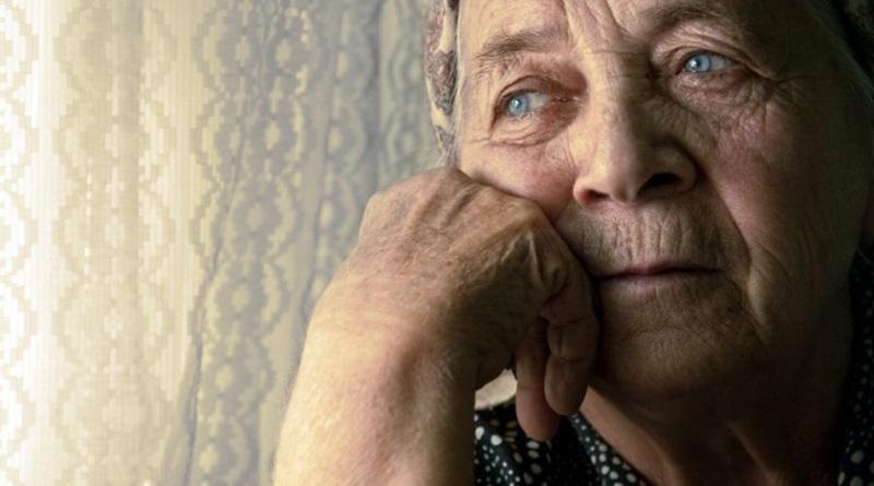 imagem de uma senhora idosa olhando pela janela