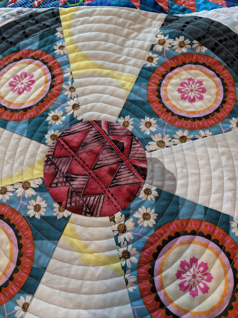 Center is re-quilted by following the print with a walking foot and transitioning to a spiral when the diameter is larger.