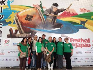 Equipe dos Cuidados Integrativos no Festival do Japão 2016, posando diante do painel de abertura do evento
