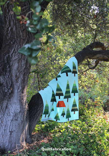 QuiltFabrication's The Great Outdoors camping quilt hanging on a tree limb