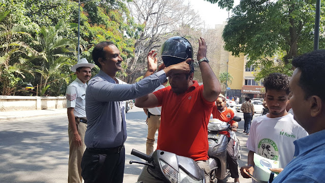 Dr Vishnuvardhan PS (facility director,Fortis) giving helmet to a biker