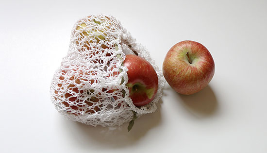 Hand knit white cotton lace produce bag with apples inside and next to it on a white background.