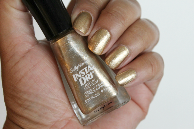 a woman hand wearing gold nail polish