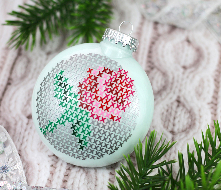 Cut craft vinyl with your Silhouette machine and layer it on a clear glass ornament to create a cross stitch design
