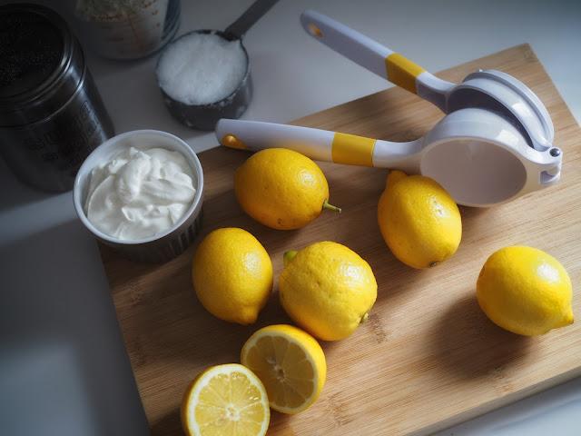 Tabla de cocina con limones, yogur, azucar y un exprimidor