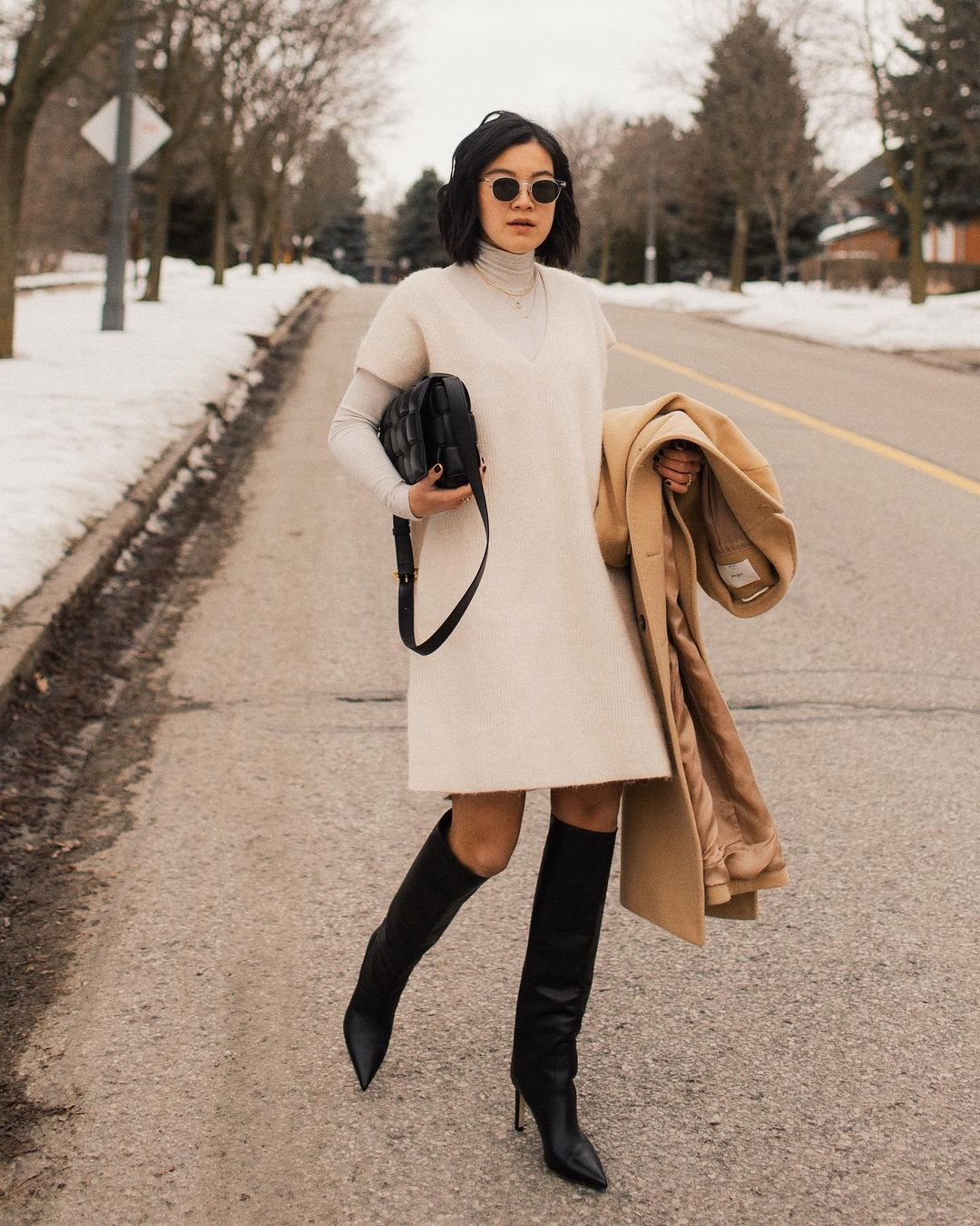 Here's How to Elevate Your Sweaterdress This Fall — @jessundecided Instagram outfit idea with a white sweater dress, layered turtleneck, camel coat, and black knee-high boots with pointed toe