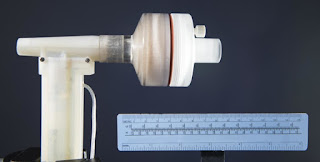 Prototype of NO generator. Air is taken in through the  inlet on the left and passes by the electrode at the top  of the vertical segment, where a series of sparks  generates NO gas. The cylindrical chamber contains  calcium hydroxide and a filter to remove toxic byproducts  before the NO-enriched air exits on the right to be inhaled  by the patient. Credit: Brian Wilson, Massachusetts  General Hospital Photography Department