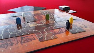 A game of Tsuro in progress. The photo shows the board, with several tiles laid out upon it, and the players' pieces on the tiles ready for the next player's turn.