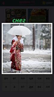 по снегу идет женщина в национальной одежде под зонтиком