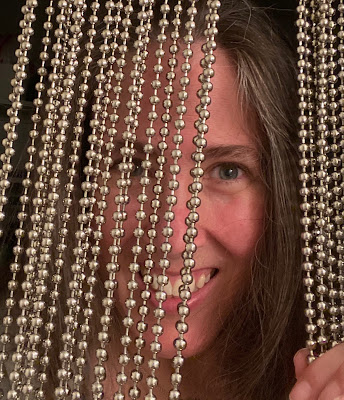 Photo of me standing behind the curtain. I'm smiling and there is a gap where I'm holding the beads aside.