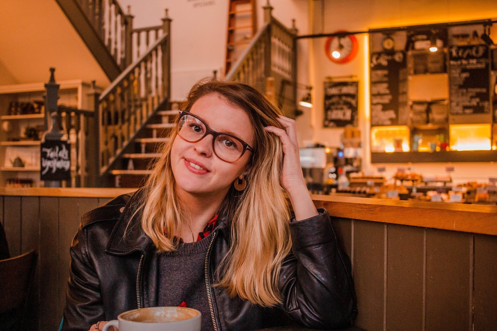 blonde girl chloeharriets in leather jacket and thick rimmed glasses, in coffee shop smiling for lifestyle blog picture, new year new start, blog rebrand