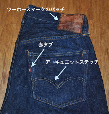 Pointing Levi's jeans identities including two-horse brand patch, arcuate stitch, and red tab on Levi's 501xx