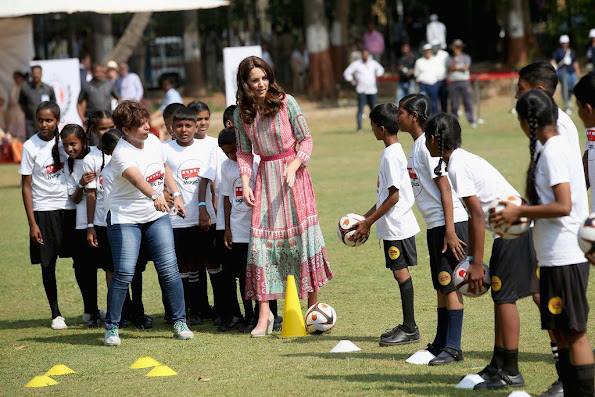 Catherine, Duchess of Cambridge joins in with ball games during a visit to meet children from Magic Bus