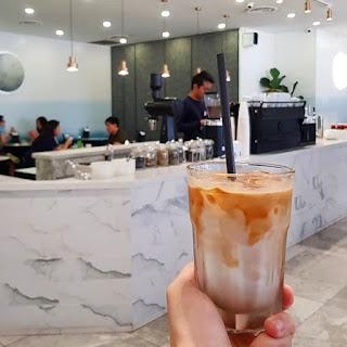Hand holding iced glass coffee