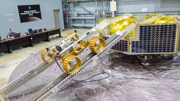 A test unit of the VIPER lunar rover rolls down the ramp of a full-scale replica of Astrobotic's Griffin Moon lander...at NASA's Johnson Space Center in Houston, Texas.