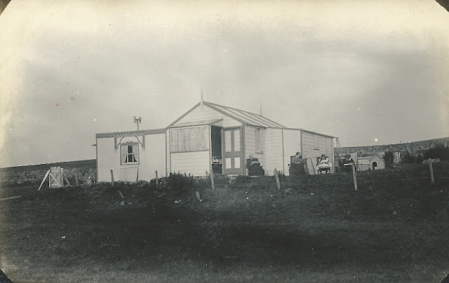 People seated outside a wooden chalet