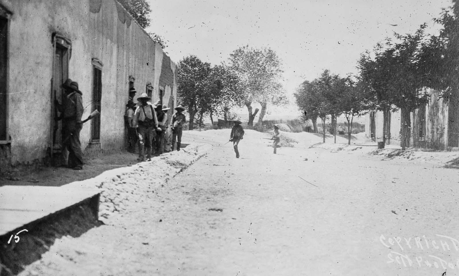 Rebel fighters dash across a Juárez street under fire.