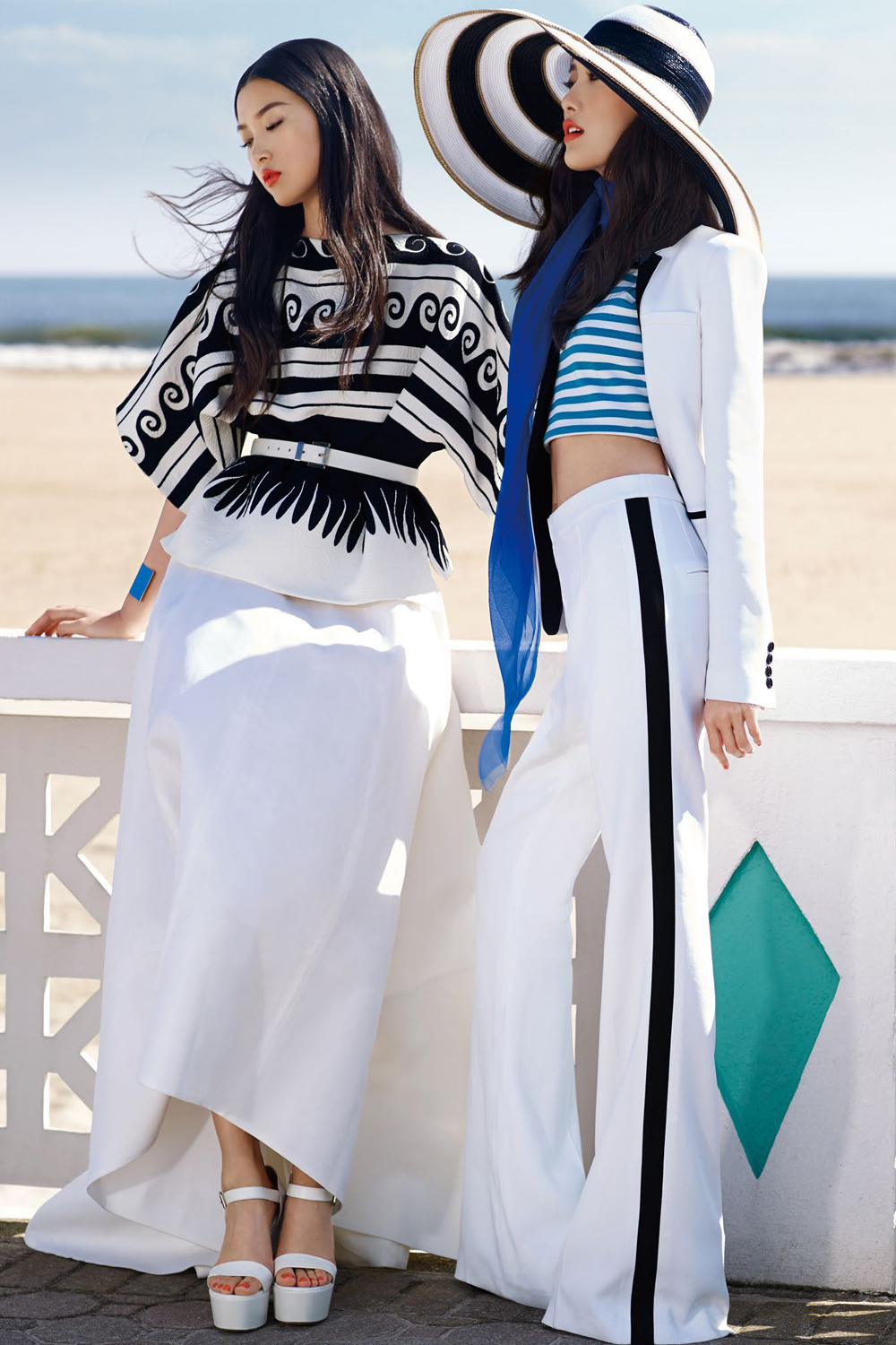 two women wearing nautical outfits are posing on the beach