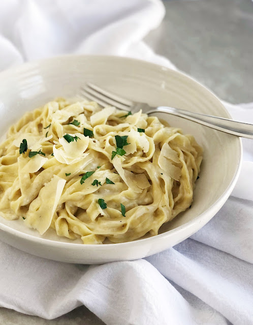fresh homemade pasta with creamy alfredo sauce garnished with parsley and parmasan cheese