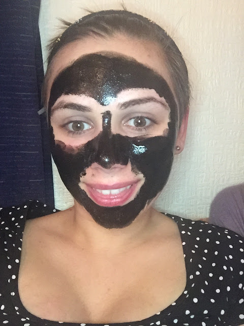 women wearing a black peel off face mask treatment