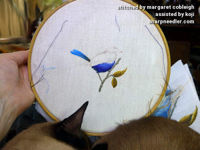 The bird's breast is half stitched in blues. My Siamese cat, Koji, is sleeping in the foreground.