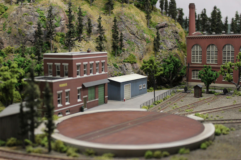 Completed industrial scene made up of a Cutting Scissors Co kit and scratch built garage next to an Atlas turn table