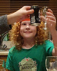 small boy with fancy port glass full of cola chinking glasses in a toast with others off screen