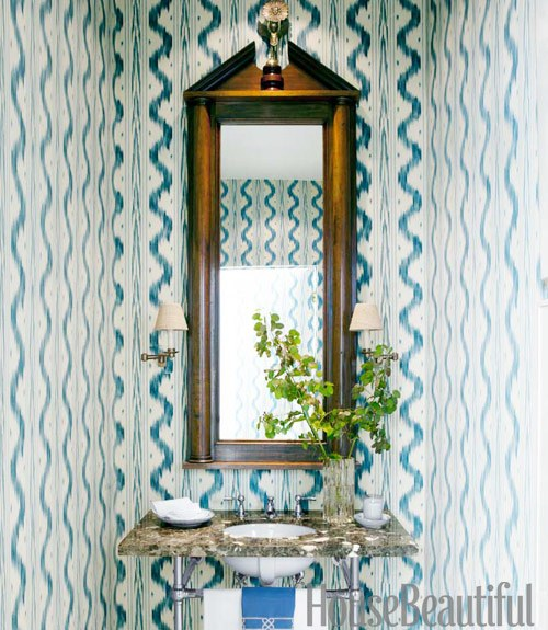 Blue and white toile de Nantes wallpaper in a small powder room with pedestal sink and granite counter top and tall mirror with wooden frame