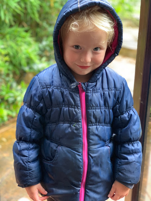 3 year old wearing a winter coat by the back door with a rainy garden in the background