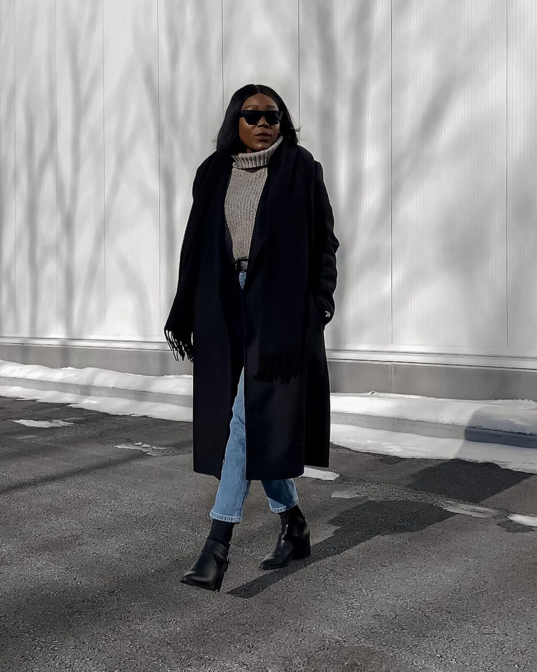 Stylish Winter Outfit Idea From Instagram — Sabrinah Edouard in a black coat, gray turtleneck sweater, jeans, and black boots