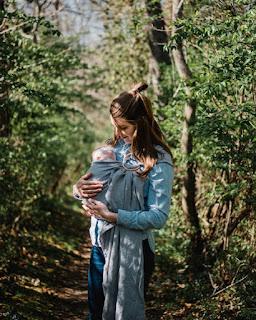 Maman qui porte son bébé avec un sling doté d'anneaux
