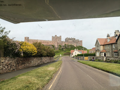 Photo taken from the motorhome passenger seat, whilst moving. It shows Bamburgh Castle right in front of us.