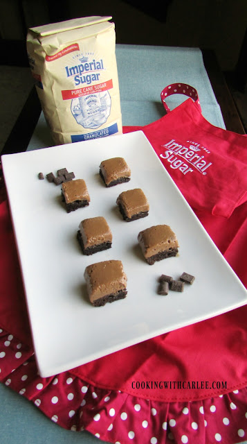 squares of french silk brownies on rectangle platter with imperial sugar bag and apron in background