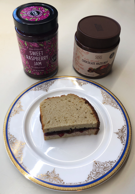 Photo of half sandwich made with keto bread, keto jam, and keto chocolate hazelnut spread
